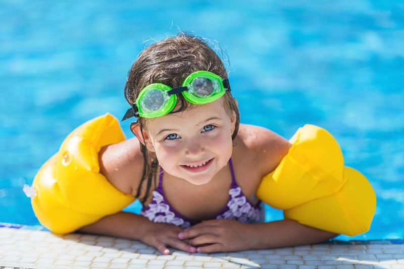 little girl with pool floaties, pool safety tips