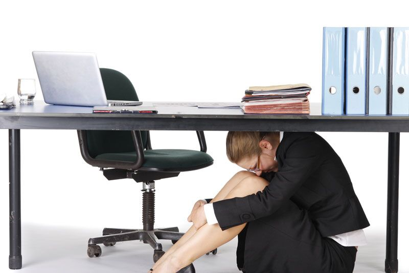 stressed woman hiding under her desk, manage work stress