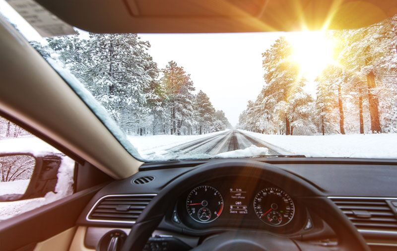 car driving on snowy roads, take care of your car this winter