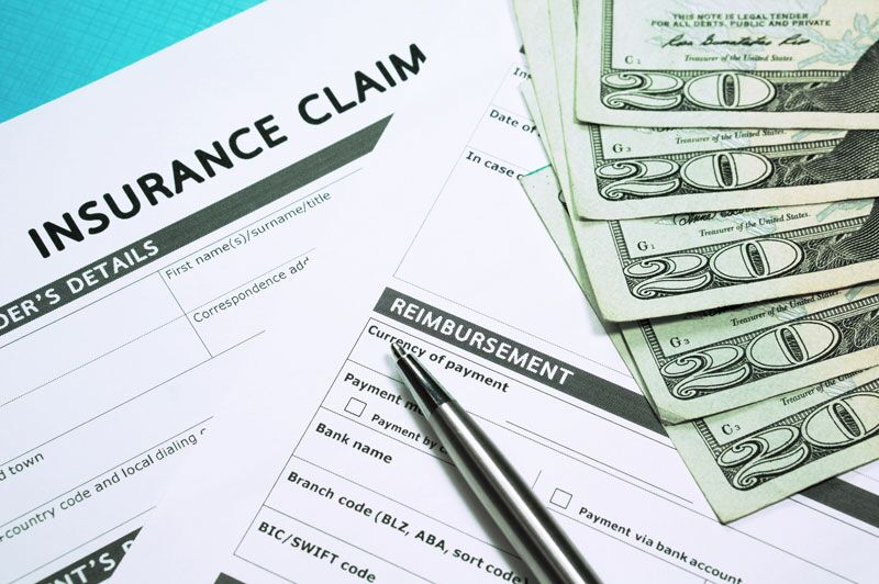 insurance claim forms surrounded by money, common mistakes to avoid when filing a business insurance claim